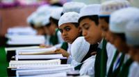 Ekspresi anak-anak muslim saat mengikuti baca Alquran berjemaah selama bulan Ramadan di Masjid Imam Ali Ibn Abi Tholib di Najaf, Irak (2/6). (AFP/Haidar Hamdani)