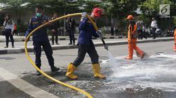 Petugas Damkar dan Pasukan Oranye melakukan pembersihan sisa residu gas air mata dari badan jalan MH Thamrin dekat Gedung Bawaslu, Jakarta, Kamis (23/5/2019). Sebelumnya, aksi unjuk rasa yang dilakukan massa pada Rabu (22/5) berakhir ricuh. (Liputan6.com/Helmi Fithriansyah)