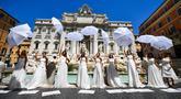 Pengantin perempuan yang mengenakan gaun pernikahan mereka melakukan flashmob saat aksi protes di Trevi Fountain, Roma, Selasa (7/7/2020). Mereka memprotes kebijakan pemerintah Italia yang masih melarang adanya acara pernikahan, meski penerapan lockdown sudah dilonggarkan. (Tiziana FABI/AFP)
