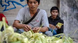 Seorang pedagang saat menata kulit ketupat dagangannya di sebuah pasar kawasan Ciracas, Jakarta, Kamis (16/7/2015). Menjelang Lebaran, warga mulai ramai membeli kulit ketupat. (Liputan6.com/Faizal Fanani)