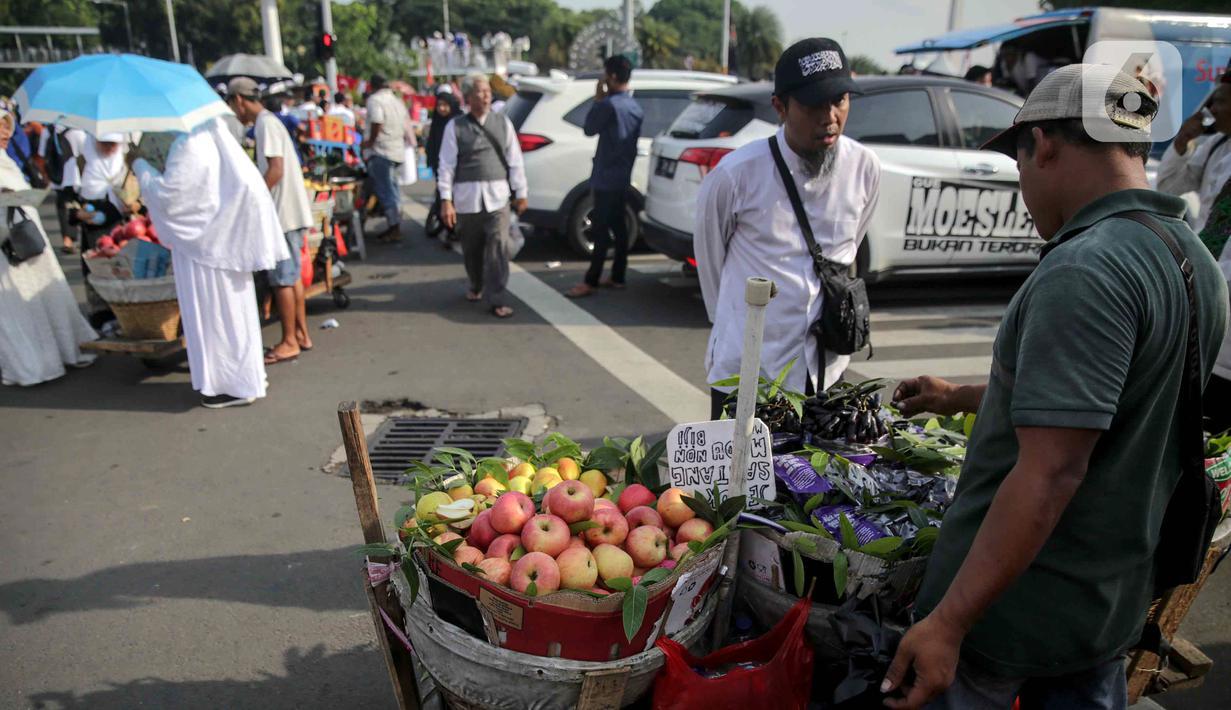Pedagang buah melayani pembeli saat berjualan di tengah aksi reuni 212, sekitaran Jalan Medan Merdeka Barat, Jakarta, Senin (2/12/2019). Sejumlah PKL meraup untung dengan berjualan di tengah ribuan massa Persaudaraan Alumni 212 yang mengikuti reuni di Monas. (Liputan6.com/Faizal Fanani)