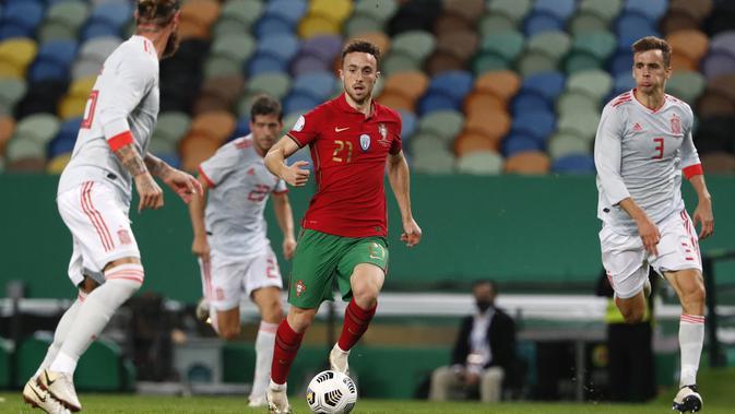 Gelandang Portugal, Diogo Jota (tengah) membawa bola saat bertanding melawan Spanyol pada pertandingan persahabatan di stadion Jose Alvalade di Lisbon, Rabu (7/10/2020). Spanyol bermain imbang 0-0 atas Portugal. (AP Photo/Armando Franca)