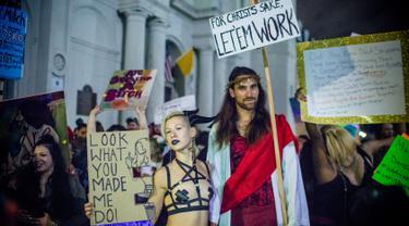 Sejumlah orang membawa poster melakukan demonstrasi di Bourbon Street, New Orleans (1/2). Aksi demonstrasi ini dilakukan oleh para penari, pekerja klub malam dan pendukungnya. (AFP/Emily Kask)