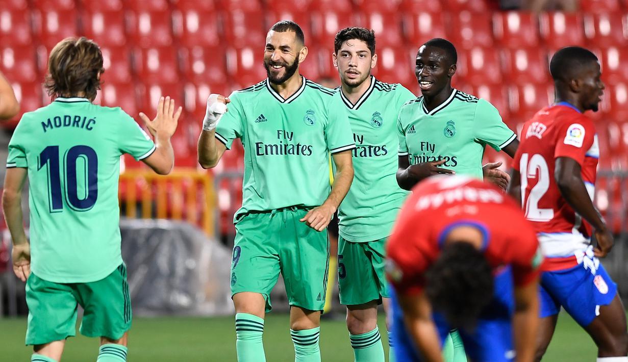 Penyerang Real Madrid, Karim Benzema (kedua kiri) berselebrasi usai mencetak gol ke gawang Granada pada pertandingan lanjutan La Liga Spanyol  di stadion Nuevo Los Carmenes di Granada (13/7/2020). Madrid menang tipis 2-1 atas Granada. (AFP/Jorge Guerrero)