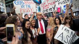Sejumlah wanita seksi berbikini mengililingi seniman berpenampilan seperti Donald Trump saat unjuk rasa di depan Times Square, New York (25/10). Aksi ini dilakukan oleh seniman Alison Jackson. (AFP Photo/Drew Angerer/Getty Images)