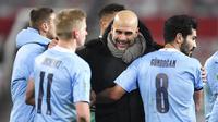 Pelatih Manchester City, Pep Guardiola, merayakan kemenangan atas Manchester United pada laga Piala Liga Inggris di Stadion Old Trafford, Rabu (6/1/2021). City menang dengan skor 2-0. (Peter Powell/Pool via AP)