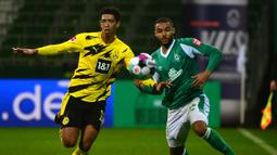 Gelandang Werder Bremen, Jean-Manuel Mbom (kanan), berebut bola dengan gelandang Borussia Dortmund, Jude Bellingham, dalam laga lanjutan Bundesliga Liga Jerman 2020/21 pekan ke-12 di Weserstadion, Bremen, Selasa (15/12/2020). Bremen kalah 1-2 dari Dortmund. (AFP/Patrik Stollarz/Pool).