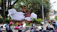 Aremania menutup dua patung singa dan menyisakan satu patung saja dalam aksi yang digelar di depan Stasiun Kota Baru Malang, Senin (16/11/2020). (Bola.com/Iwan Setiawan)