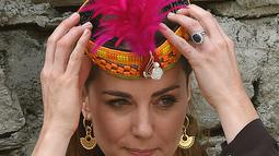Duchess of Cambridge, Kate Middleton marapikan topi tradisional suku Kalash selama kunjungannya ke Lembah Bumburate di Distrik Chitral utara Pakistan (16/10/2019). Kate Middleton tampil cantik berpenampilan dengan topi tradisional Suku Kalash. (AFP Photo/Farooq Naeem)