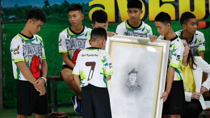 12 anak laki-laki dan pelatih sepak bola mereka, yang diselamatkan dari gua banjir di Thailand, memberi penghormatan terhadap lukisan penyelam AL Thailand yang meninggal selama operasi penyelamatan di Chiang Rai, Rabu (18/7). (AP/Vincent Thian)