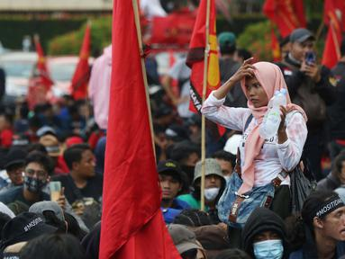 Pedagang asongan berjualan di tengah-tengah aksi unjuk rasa di kawasan Patung Kuda, Jakarta, Selasa (10/11/2020). Sejumlah pedagang mencoba peruntungan saat massa gabungan dari berbagai organisasi buruh dan mahasiswa berunjuk rasa menolak Omnibus Law UU Cipta Kerja. (Liputan6.com/Helmi Fithriansyah)