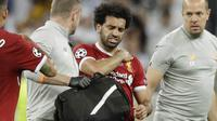 Striker Liverpool, Mohamed Salah, memegang bahu nya saat ditarik keluar lapangan pada laga final Liga Champions di Stadion NSC Olimpiyskiy, Kiev, Minggu (27/5/2018). Salah mengalami cedera bahu usai dilanggar Ramos. (AP/Matthias Schrader)