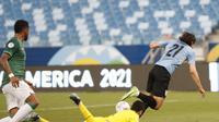 Pemain Uruguay Diego Godin, kiri, berebut bola dengan pemain Bolivia Rodrigo Ramallo selama pertandingan sepak bola Copa America di Arena Pantanal di Cuiaba, Brasil, Kamis, 24 Juni 2021. (AP Photo/Andre Penner)