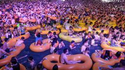 Corona Berlalu, Warga Wuhan Pesta di Kolam: Orang-orang menonton pertunjukan musik sambil bermain air di sebuah taman air atau water park di Wuhan, provinsi Hubei, China, 15 Agustus 2020. Mereka berpesta saat Wuhan kembali ke kehidupan normal setelah sempat terdampak parah oleh COVID-19. (STR/AFP)