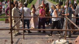 Turis melewati reruntuhan puing-puing pilar Taj Mahal yang roboh di pintu masuk bangunan ikonik tersebut di Agra, India, Kamis (12/4). Angin kencang dengan kecepatan 130 kilometer per jam menyebabkan pilar setinggi 4 meter itu runtuh. (AP/Pawan Sharma)