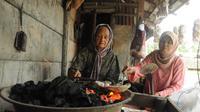 Husni membakar Kemplang Palembang yang mentah di atas bara api (Liputan6.com / Nefri Inge)