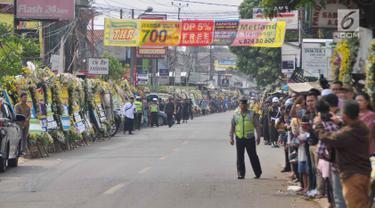 Warga sekitar Puri Cikeas bersiap menyambut iring-iringan kepergian jenazah Ani Yudhoyono menuju TMP Kalibata, Bogor, Jawa Barat, Minggu (2/6/2019). Ani Yudhoyono dimakamkan di TMP Kalibata. (Liputan6.com/Immanuel Antonius)