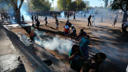Para demonstran antipemerintah berkumpul di antara gas air mata yang ditembakkan polisi untuk membubarkan protes di Santiago, Chile, Jumat (27/12/2019). Protes Chile berubah menjadi gerakan yang jauh lebih besar dan luas dengan daftar panjang tuntutan. (AP Photo/Fernando Llano)
