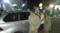 Satpol PP Tuban mengamankan sepasang anak muda dari dalam mobil untuk dimintai keterangan. Sebelumnya warga dibuat heboh dengan kejadian mobil bergoyang di depan rumah dinas Wakil Bupati Tuban. (Liputan6.com/ Ahmad Adirin)