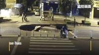 Pengendara motor melaju ke arah sinkhole di jalanan Kota Behai, Guangxi, China. (Shanghaiist)