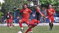 Bek Arema FC, Taufik Hidayat menghalangi pemain akademi Arema dalam sesi latihan di lapangan Balearjosari, Kota Malang. (Iawan Setiawan/Bola.com)
