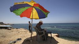 Seorang pria membaca Al-Quran bulan suci Ramadan di pantai Kota Gaza, Palestina, Jumat (1/5/2020). (MOHAMMED ABED/AFP)