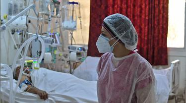 Seorang petugas medis Tunisia merawat pasien di gym yang diubah untuk menangani lonjakan infeksi COVID-19 di pusat kota Kairouan pada 4 Juli 2021. Tunisia tengah berjuang menghadapi tsunami COVID-19 sementara jumlah orang yang meninggal akibat virus corona terus melonjak tinggi. (FETHI BELAID/AFP)