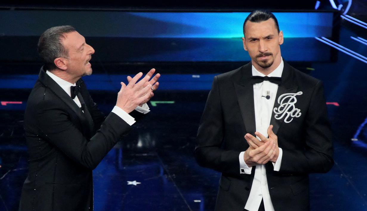 Striker AC Milan, Zlatan Ibrahimovic (kanan) dan presenter televisi Italia Amadeus tampil pada malam pembukaan festival musik San Remo di San Remo, Selasa (2/3/2021). Ibrahimovic yang sedang cedera melakukan debutnya sebagai pembawa acara di festival musik tersebut. (Marco RAVAGLI/AFP)