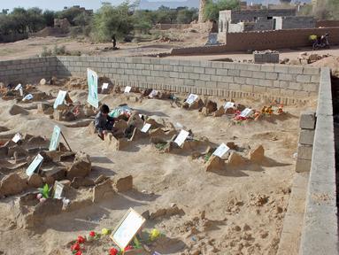Seorang anak Yaman mengunjungi makam anak-anak sekolah di sebuah pemakaman di provinsi kubu pemberontak Huthi di Saada (4/9). Anak-anak tersebut tewas terkena serangan udara koalisi pimpinan Saudi saat berada di sebuah bus. (AFP Photo/Stringer)