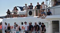 Para turis berdiri di dek kapal saat dievakuasi dari Gili Trawangan ke Pelabuhan Bangsal, Lombok Utara, NTB, Selasa (7/8). Ribuan turis asing dievakuasi dari Gili Trawangan setelah gempa Lombok. (ADEK BERRY/AFP)