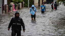 Warga melintasi banjir di jalan Pd. Karya, Jakarta, Kamis (13/12). Hujan yang mengguyur Jakarta Sore tadi menyebabkan banjir setinggi 40cm  menggenangi kawasan Jalan Pd. Karya dan Jalan Bangka. (Liputan6.com/Faizal Fanani)