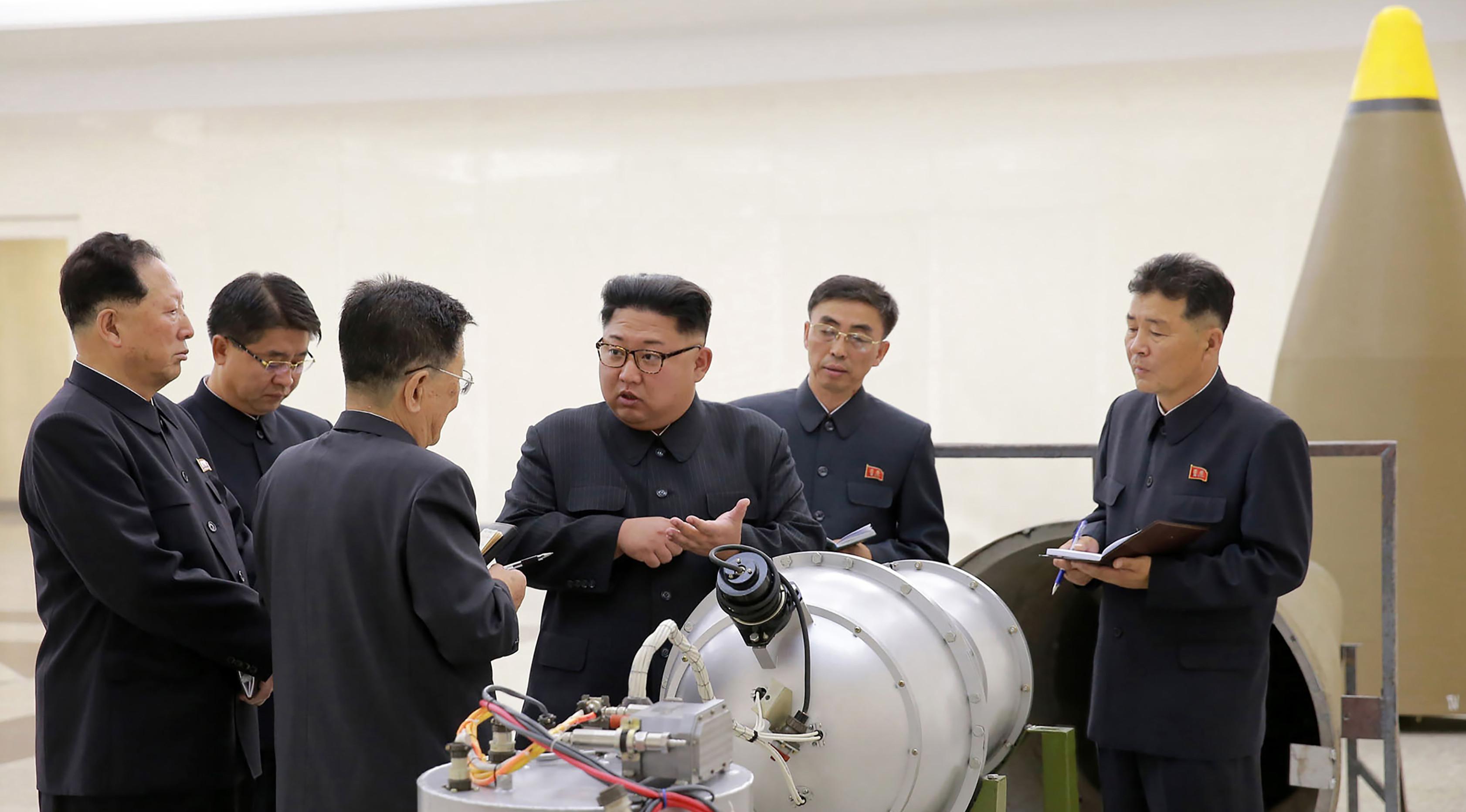 Pemimpin Korut, Kim Jong-un berbincang dengan para peneliti mengenai program senjata nuklir saat meninjau pembuatan bom hidrogen yang dapat dimasukkan ke dalam rudal balistik antarbenua pada 3 September 2017. (AFP Photo/Kcna Via Kns/Str)