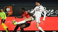 Striker Rennes, Jeremy Doku (kiri) berebut bola dengan gelandang Nice, Pierre Lees-Melou dalam laga lanjutan Liga Prancis 2020/21 pekan ke-27 di Roazhon Park Stadium, Rennes, Jumat, (26/2/2021). Rennes kalah 1-2 dari Nice. (AFP/Damien Meyer)