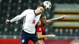 Pemain Inggris, Jack Grealish, duel udara dengan pemain  Belgia, Toby Alderweireld, pada laga UEFA Nations League di Stadion King Power, Senin (16/11/2020). Belgia menang dengan skor 2-0. (AP/Francisco Seco)