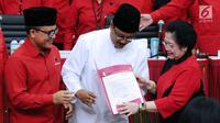 Ketua Umum PDIP Megawati Soekarno Putri (kanan) menyerahkan surat rekomendasi pada Pasangan Cagub-Cawagub Jawa Timur, Saifullah Yusuf (baju putih) dan Abdullah Azwar Anas usai ditetapkan di Jakarta, Minggu (15/10). (Liputan6.com/Helmi Fithriansyah)