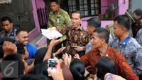 Presiden RI Joko Widodo membagikan buku tulis kepada warga di sekitar Lapangan Bedeng, Pisangan Baru, Jakarta, Selasa (8/9/2015). Kedatangan Presiden Jokowi untuk memberikan sejumlah paket sembako dan buku kepada warga. (Liputan6.com/Helmi Fithriansyah)