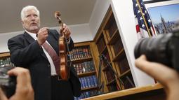 Ahli biola, Phillip Injeian menjelaskan biola Stradivarius pada konferensi pers di New York, Kamis (6/8/2015). Biola yang dibeli dengan harga Rp2,7 miliar itu kembali ke pemiliknya setelah hilang dicuri selama 35 tahun. (REUTERS/Shannon Stapleton)