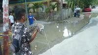 Kelurahan Dulalowo, Kota Gorontalo, provinsi Gorontalo, menaruh seekor buaya di jalan yang rusak itu. (Liputan6.com/Andri Arnold)