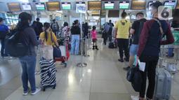 Sejumlah calon penumpang memadati loket check in Terminal3 Bandara Soekarno Hatta, Tangerang, Banten, Jumat (18/12/2020). PT Angkasa Pura II (Persero) atau AP II memprediksi lalu lintas sebanyak 2,1 juta penumpang pada periode angkutan Natal dan Tahun Baru 2021. (Liputan6.com/Angga Yuniar)