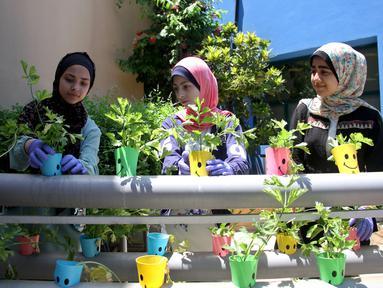 Anak-anak Palestina merawat tanaman dalam cangkir plastik di Pusat Anak-Anak Al-Qattan, Gaza City, Senin (20/7/2020). Anak-anak Palestina belajar bagaimana memanfaatkan kembali botol dan wadah plastik bekas untuk dekorasi taman. (Xinhua/Rizek Abdeljawad)