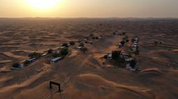 Pemandangan dari udara menunjukkan desa Al-Madam yang ditinggalkan, berbatasan dengan Emirat Teluk Sharjah, setengah terkubur di pasir gurun, Kamis (22/4/2021). Tanpa alasan yang jelas, desa tersebut ditinggalkan penduduknya begitu saja yang membuatnya kini bak kota hantu. (GIUSEPPE CACACE/AFP)