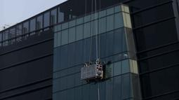 Pekerja menggunakan gondola membersihkan kaca gedung bertingkat di Jakarta, Rabu (2/10/2019). BPJS Ketenagakerjaan mencatat, sepanjang 2018 jumlah kecelakaan kerja yang dilaporkan mencapai 173.105 kasus dengan klaim Jaminan Kecelakaan Kerja (JKK) sebesar Rp 1,2 triliun. (Liputan6.com/Faizal Fanani)