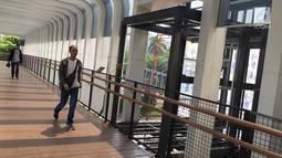 Pejalan kaki melintas di dekat pembangunan lift pada jembatan penyeberangan orang di Jakarta, Senin (13/5). Pembangunan lift pada tiga JPO yang berada di Jalan Sudirman itu bertujuan meningkatkan kenyamanan kepada warga dan ditargetkan rampung akhir bulan ini.(Liputan6.com/Immanuel Antonius)