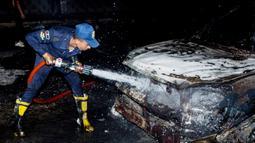 Petugas pemadam kebakaran menyemprot kendaraan yang terbakar di lokasi kebakaran pipa minyak mentah di Kairo, ibu kota Mesir (14/7/2020). Sebanyak 17 orang terluka akibat insiden kebakaran pipa minyak mentah di Kairo, demikian disampaikan Kementerian Kesehatan Mesir. (AP Photo/Alaa Ahmed)