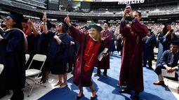 Peserta wisuda menari saat menyaksikan Jon Bon Jovi pada pesta kelulusan Universitas Fairleigh Dickinson di New Jersey, AS, Selasa (16/5). Jon Bon Jovi memberikan kejutan kepada undangan dan peserta wisuda di universitas tersebut. (AP Photo/Julio Cortez)