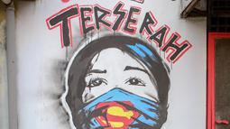 "Warga melintas di depan mural bertuliskan ""Indonesia terserah"", di Kutabumi, Tangerang, Banten, Senin (27/5/2020). Mural dibuat sebagai bentuk kritik terhadap masyarakat yang tetap beraktivitas di luar ruangan tanpa prosedur protokol kesehatan di tengah wabah COVID-19. (Liputan6.com/Angga Yuniar)"