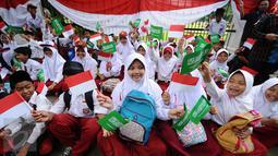 Pelajar SD mengibarkan bendera kedua negara untuk menyambut kedatangan Presiden Joko Widodo bersama Raja Arab Saudi, Salman bin Abdulaziz di sekitar Istana Bogor, Rabu (1/3). Puluhan ribu pelajar akan menyambut. (Liputan6.com/Helmi Fithriansyah)