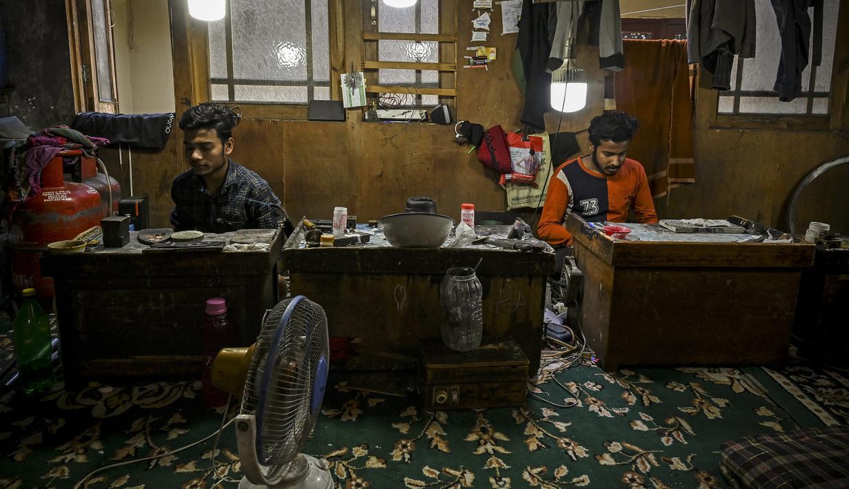 Perajin membuat ornamen di bengkel perhiasan emas di Srinagar (24/6/2021). Srinagar merupakan menjadi salah satu pusat industri kerajinan perhiasan emas. (AFP/Tauseef Mustafa)