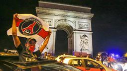 Seorang suporter mengibarkan bendera Paris Saint Germain (PSG) saat merayakan keberhasilan lolos ke final Liga Champions di Paris, Rabu (19/8/2020). Berkat kemenangan atas RB Leipzig, PSG untuk pertama kalinya berhasil lolos ke final Liga Champions. (AP/Michel Euler)