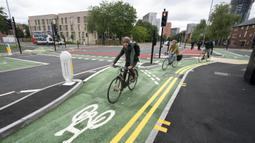 Orang-orang bersepada di jalur sepeda persimpangan CYCLOPS (Cycle Optimized Protected Signals) di wilayah selatan Manchester, Inggris (9/10/2020). Persimpangan CYCLOPS diluncurkan dengan desain unik yang memisahkan pejalan kaki dan pesepeda dari lalu lintas. (Xinhua/Jon Super)